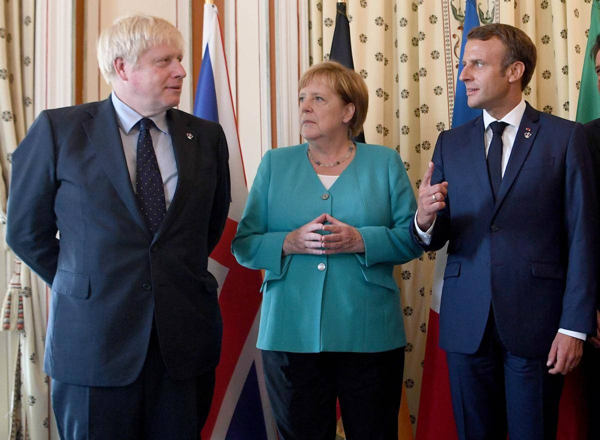British Prime Minister Boris Johnson, German Chancellor Angela Merkel and French President Emmanuel Macron pose during a G7 coordination meeting at the Hotel du Palais on 24 August 2019 in Biarritz, France. Photo credit: Pool/Getty Images