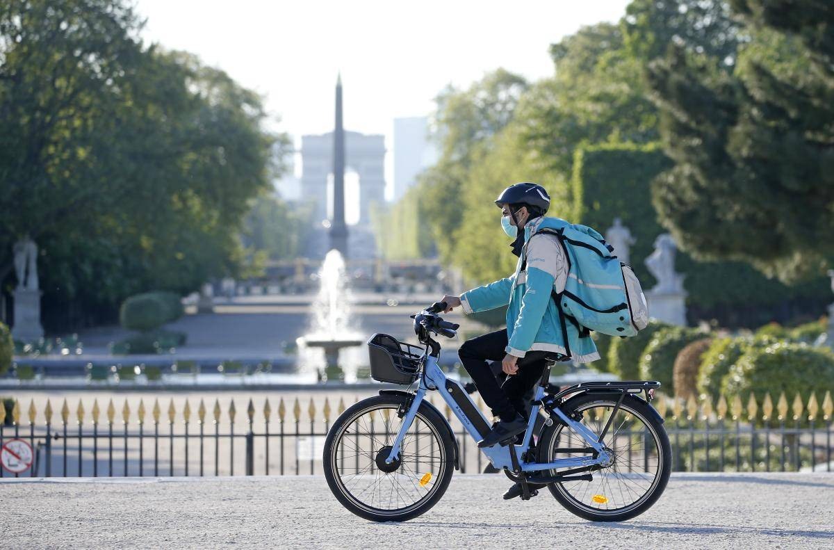 A Deliveroo rider wearing a protective mask rides his bike in the Jardin des Tuileries, Paris, 15 April 2020. Photo: © Chesnot/Getty Images