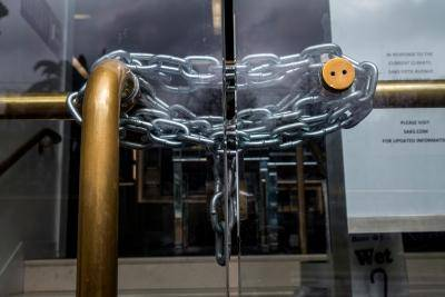 Chain wrapped around the door of a Saks Fifth Avenue Inc. store in San Francisco, California, during the COVID-19 crisis. Photo by David Paul Morris/Bloomberg via Getty Images