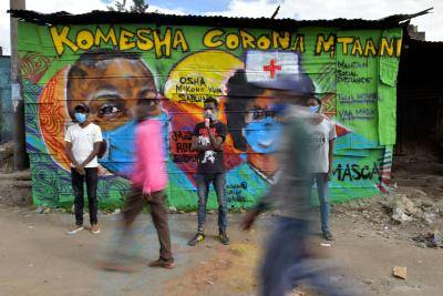 Grafitti artists from Mathare Roots Youth Organisation with their mural helping curb the spread of coronavirus in Nairobi, Kenya. Photo by TONY KARUMBA/AFP via Getty Images.